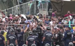 "foto: YouTube (RT), ""Riot police teargas refugees attempting to break out of detention camp in Hungary"""