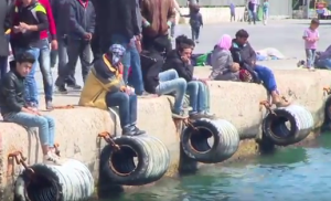 """foto: YouTube (AFPBB News), """"ギリシャのヒオス島で移民がデモ、トルコへの送還目前に Hundreds of migrants storm out of detention centre in Chios"""""""